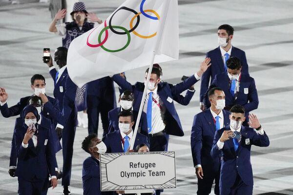 Юсра Мардини и Тахловини Габриесос несут олимпийский флаг. - Sputnik Таджикистан