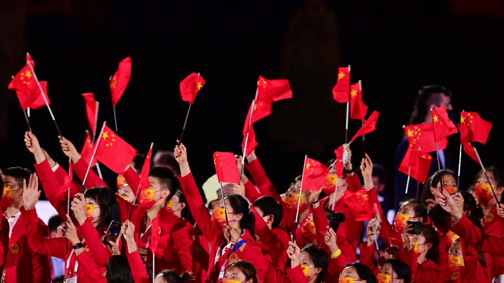 Члены китайской делегации машут флагами, входя на Олимпийский стадион во время церемонии открытия в Токио - Sputnik Таджикистан, 1920, 05.09.2021