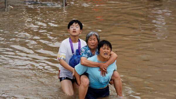 Женщина несет пожилую женщину  через паводковые воды после проливного дождя в Чжэнчжоу, провинция Хэнань, Китай - Sputnik Таджикистан