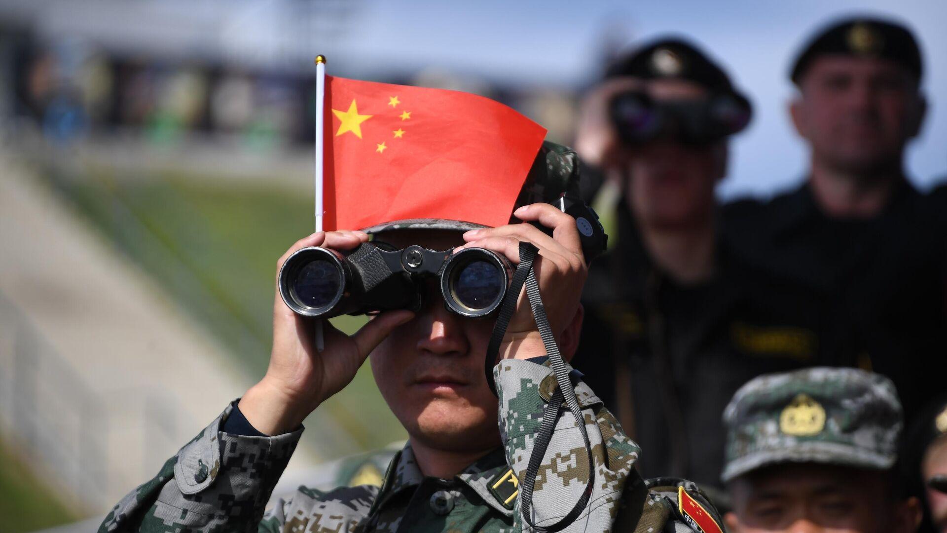 Военнослужащий армии Китая наблюдает в бинокль за соревнованиями  - Sputnik Таджикистан, 1920, 13.10.2021
