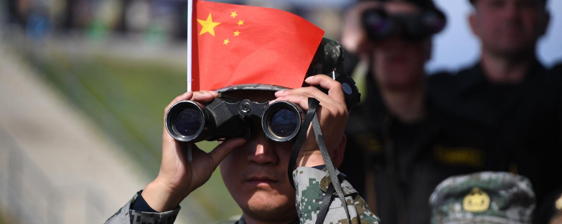 Военнослужащий армии Китая наблюдает в бинокль за соревнованиями  - Sputnik Таджикистан, 1920, 29.07.2021