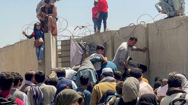 Мужчина тянет наверх девочку у аэропорта Кабула  - Sputnik Таджикистан