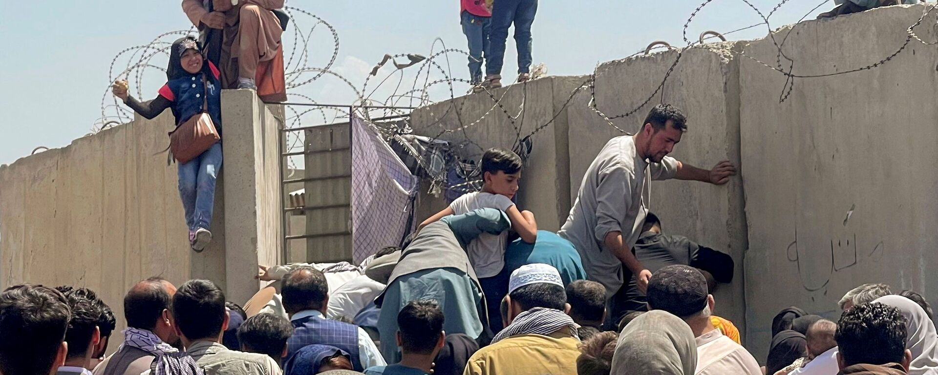 Мужчина тянет наверх девочку у аэропорта Кабула  - Sputnik Таджикистан, 1920, 22.08.2021