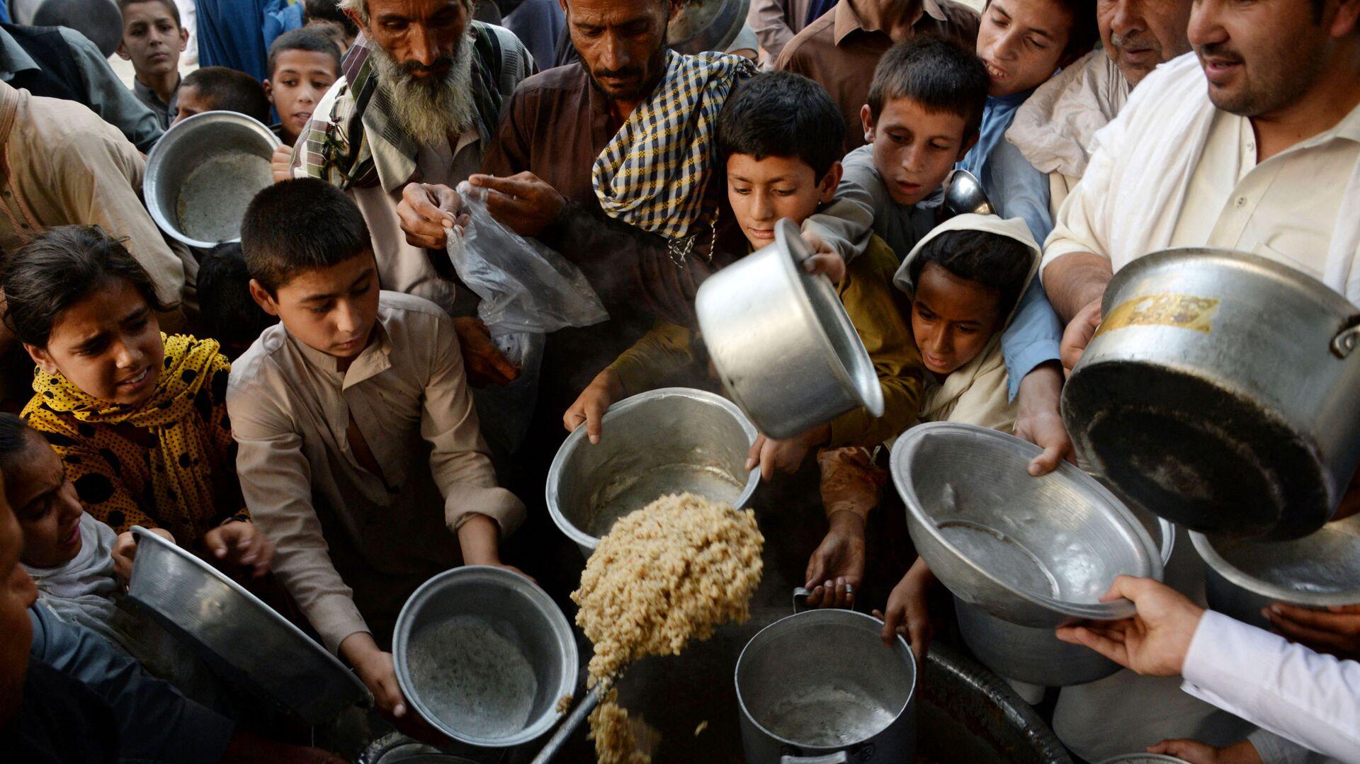 Афганские дети держат тарелки в ожидании еды в городе Джелалабад - Sputnik Тоҷикистон, 1920, 06.10.2021
