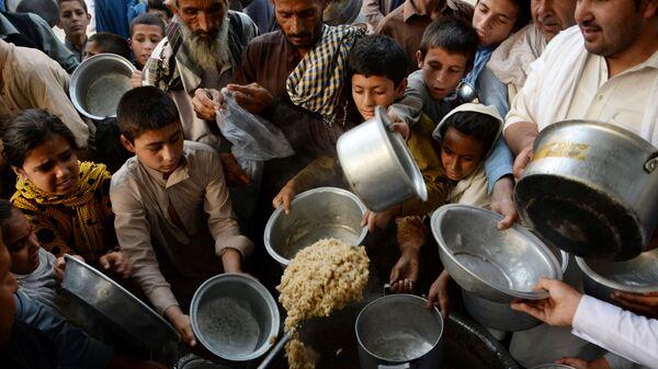 Афганские дети держат тарелки в ожидании еды в городе Джелалабад - Sputnik Тоҷикистон