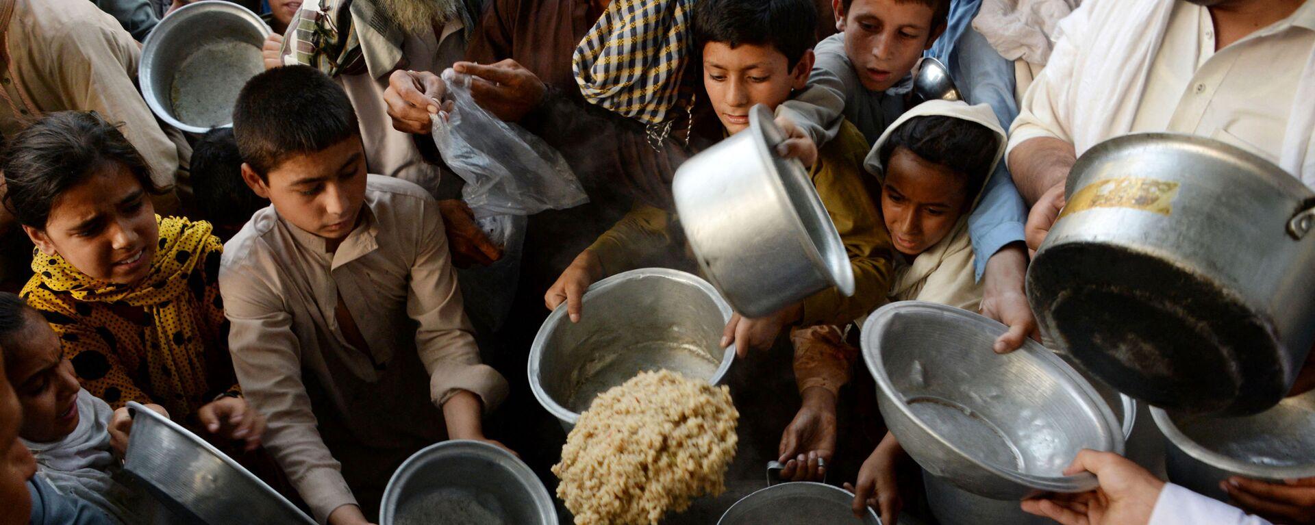 Афганские дети держат тарелки в ожидании еды в городе Джелалабад - Sputnik Тоҷикистон, 1920, 25.08.2021