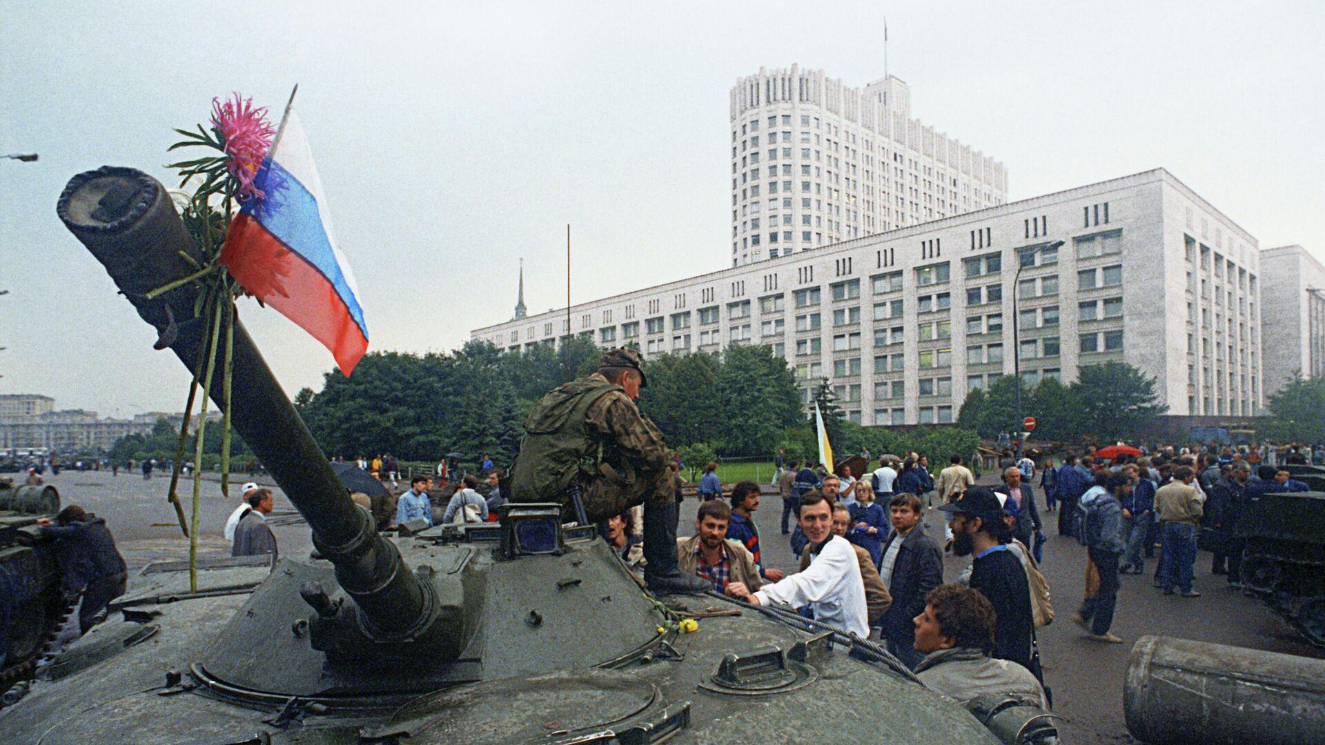 Защитники Белого дома прикрепили цветы к орудийному стволу одного из танков, введеных в Москву 19 августа 1991 года в связи с объявлением членами ГКЧП чрезвычайного положения в столице - Sputnik Таджикистан, 1920, 19.08.2021