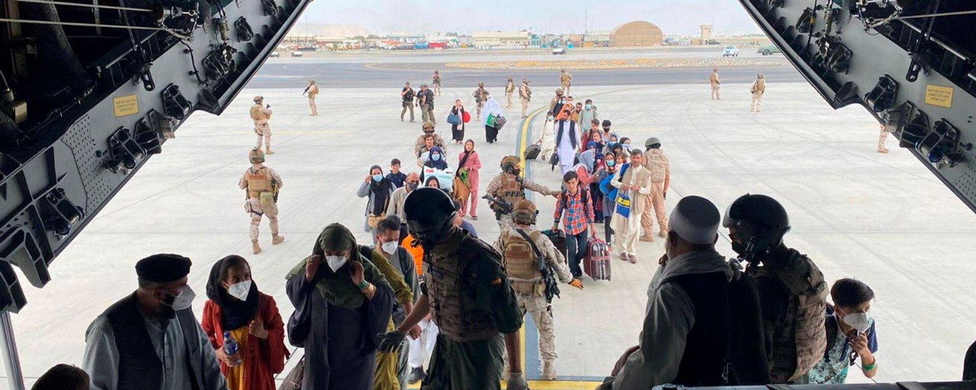 Граждане Испании и афганцы садятся в военный самолет в рамках эвакуации в международном аэропорту Хамида Карзая в Кабуле - Sputnik Таджикистан, 1920, 30.08.2021
