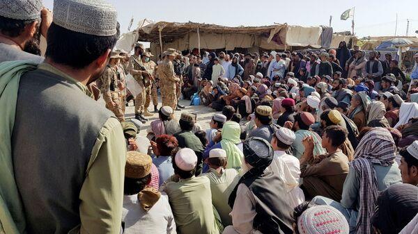 Солдаты пакистанской армии разговаривают с людьми, которые собираются пересечь пункт пропуска в пакистано-афганском пограничном городе Чаман - Sputnik Таджикистан