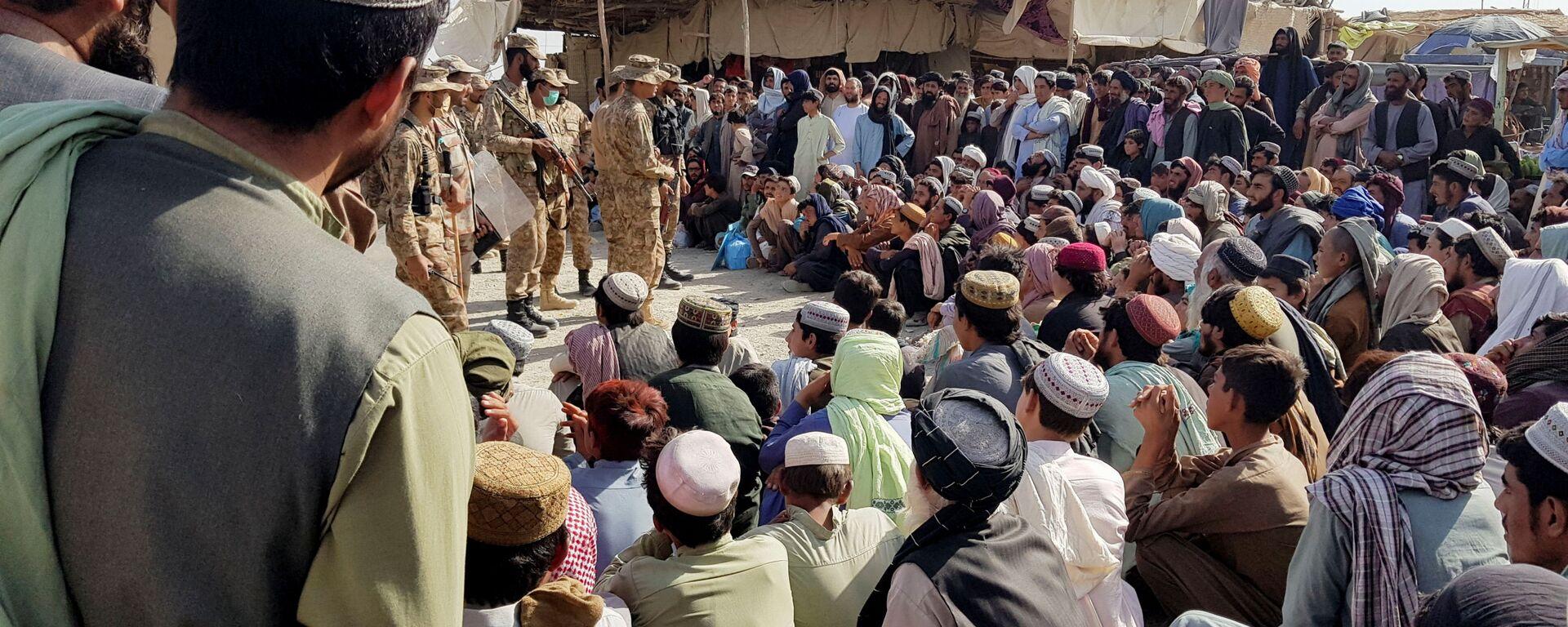 Солдаты пакистанской армии разговаривают с людьми, которые собираются пересечь пункт пропуска в пакистано-афганском пограничном городе Чаман - Sputnik Таджикистан, 1920, 06.09.2021