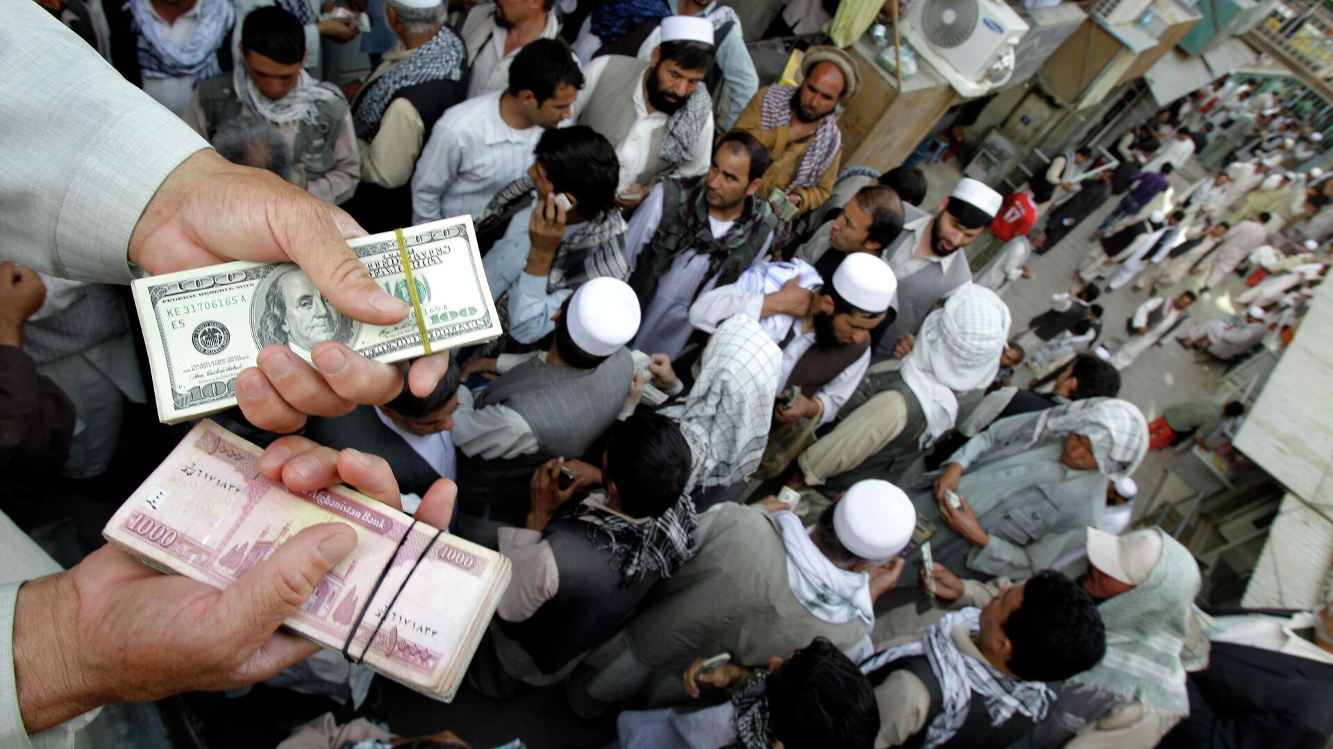 Афганский торговец держит пачки долларов США и афгани на Сарай-Шахзаде - Sputnik Таджикистан, 1920, 20.08.2021