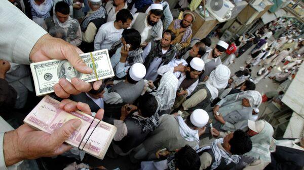 Афганский торговец держит пачки долларов США и афгани на Сарай-Шахзаде - Sputnik Таджикистан