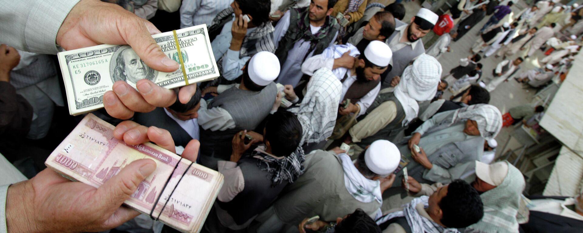 Афганский торговец держит пачки долларов США и афгани на Сарай-Шахзаде - Sputnik Таджикистан, 1920, 08.09.2021