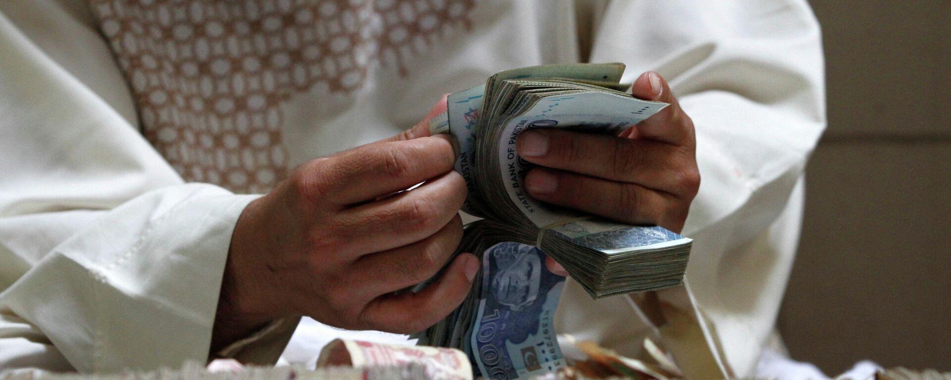 Мужчина держит в руках деньги, афгани - Sputnik Тоҷикистон, 1920, 06.10.2021