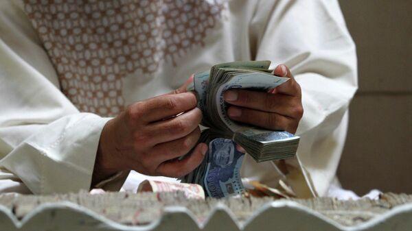Мужчина держит в руках деньги, афгани - Sputnik Тоҷикистон