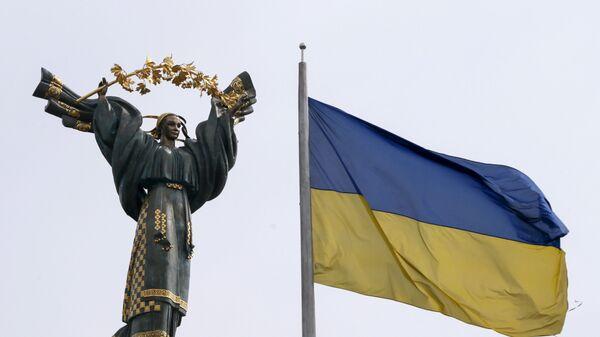 Флаг Украины на фоне Монумента Независимости на площади Независимости в Киеве - Sputnik Таджикистан