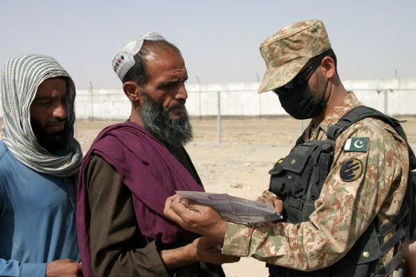 Пакистанский пограничник проверяет документы прибывших в страну афганцев. - Sputnik Таджикистан