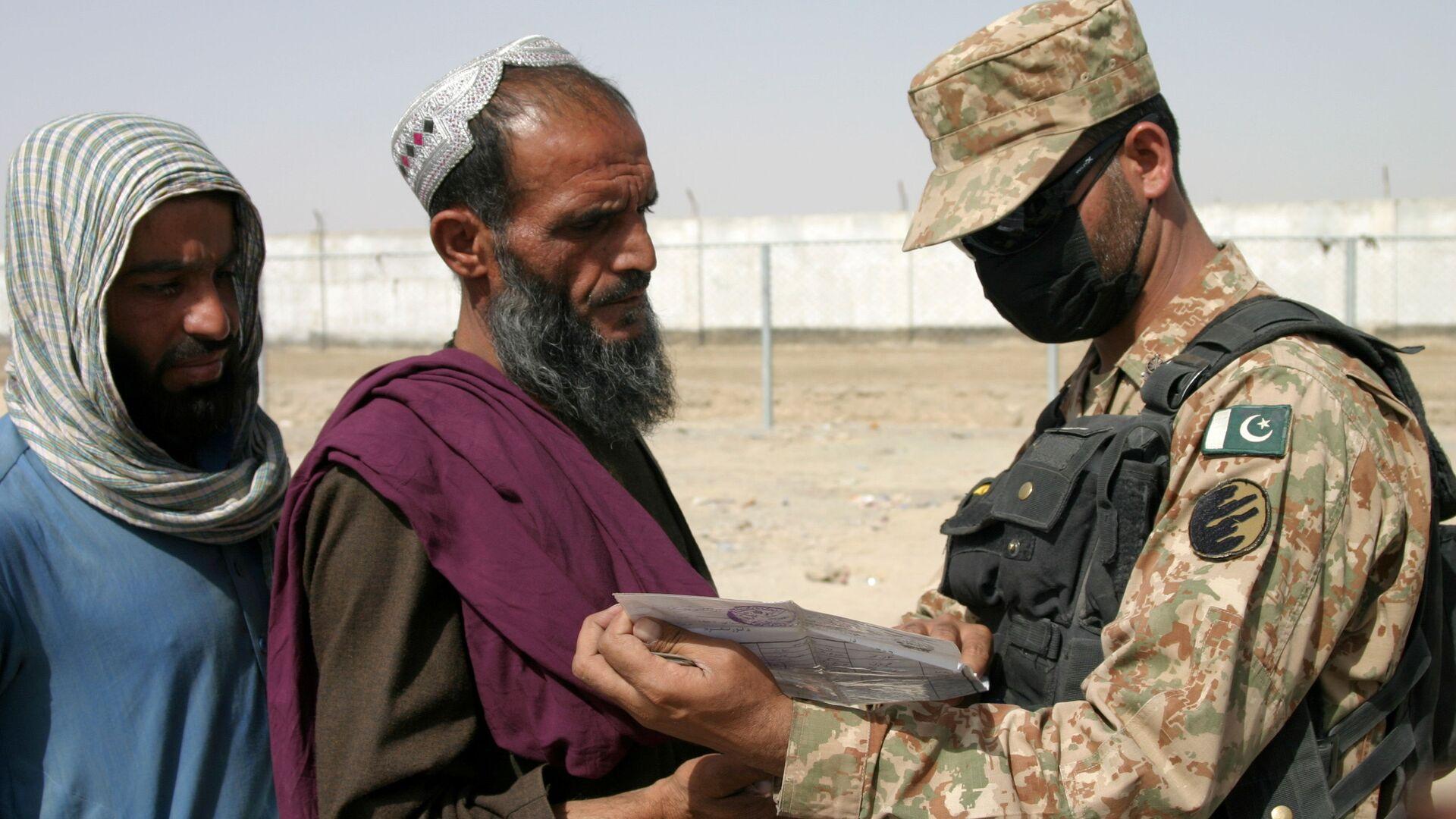 Пакистанский солдат проверяет документы людей, прибывающих из Афганистана, на контрольно-пропускном пункте Ворота дружбы в пакистано-афганском пограничном городе Чаман, Пакистан - Sputnik Таджикистан, 1920, 29.09.2021