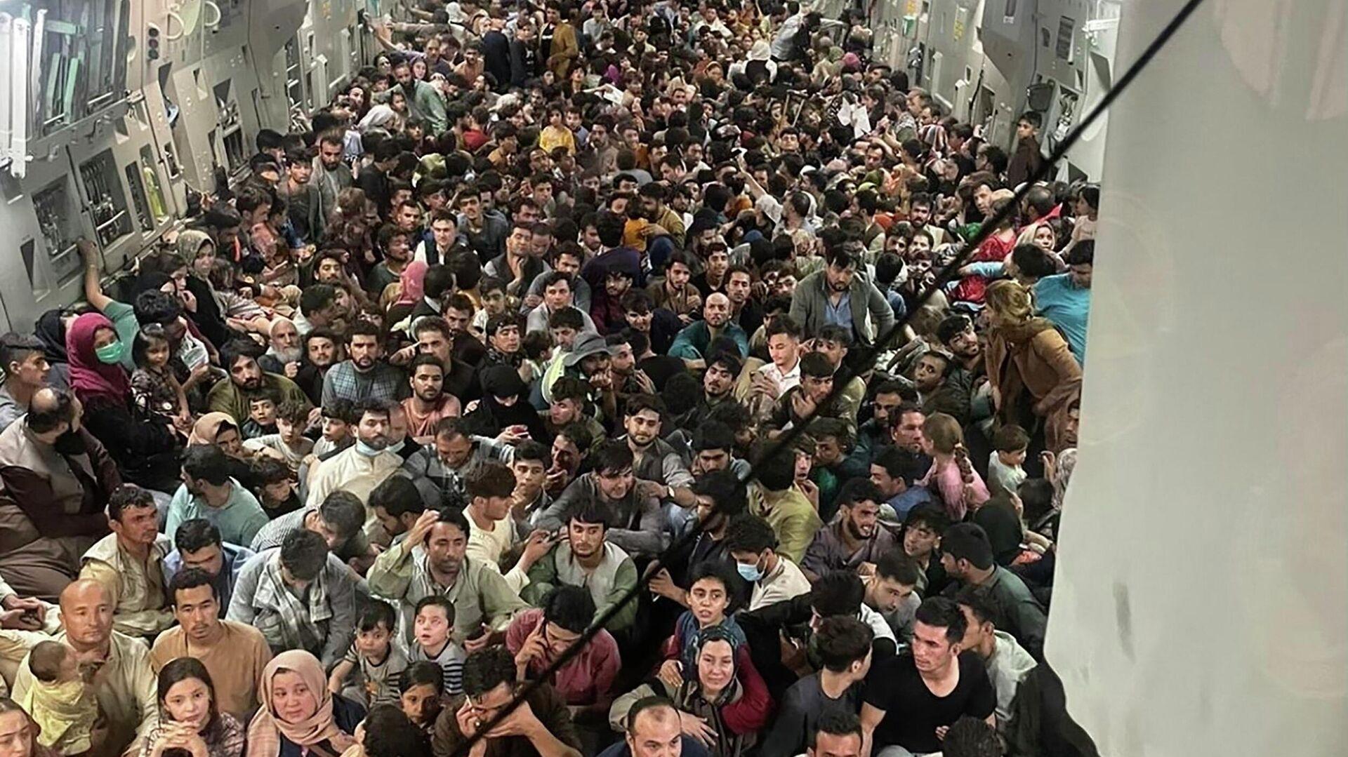 Беженцы из Афганистана в самолете - Sputnik Таджикистан, 1920, 11.10.2021