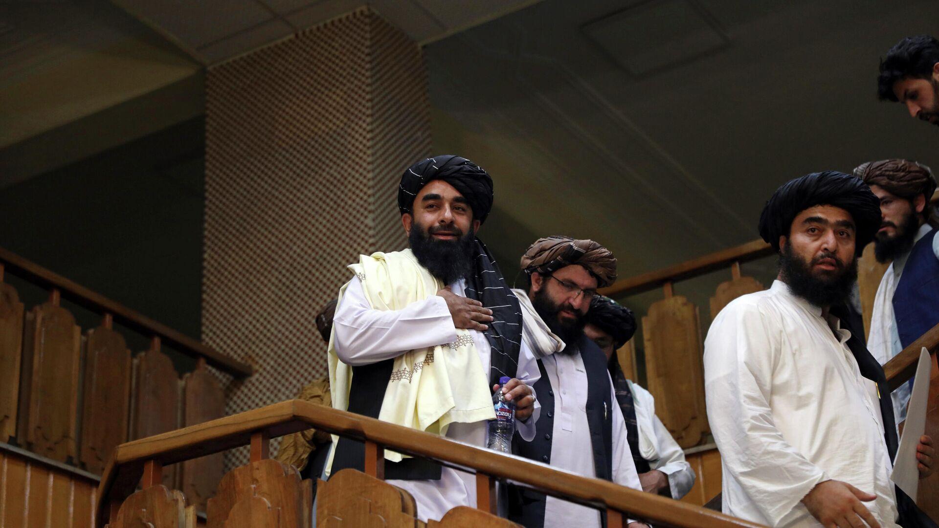 Представитель Талибана Забихулла Муджахид (слева) прибывает на свою первую пресс-конференцию в Информационный центр правительственных СМИ в Кабуле - Sputnik Таджикистан, 1920, 10.09.2021