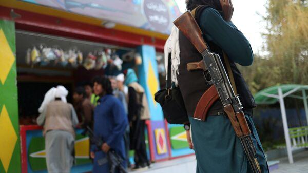 Боец Талибана* с винтовкой в парке развлечений в Кабуле - Sputnik Тоҷикистон