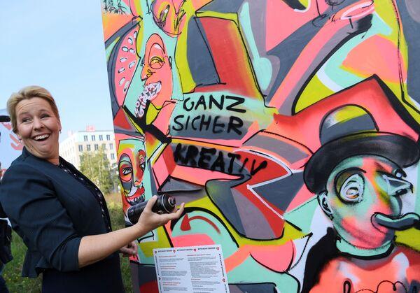 Член СДПГ Франциска Гиффи на выборах в штате Берлин реагирует на граффити. - Sputnik Таджикистан