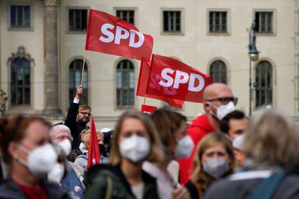 Люди машут флагами Социал-демократической партии Германии во время мероприятия, посвященного предстоящим выборам. - Sputnik Таджикистан