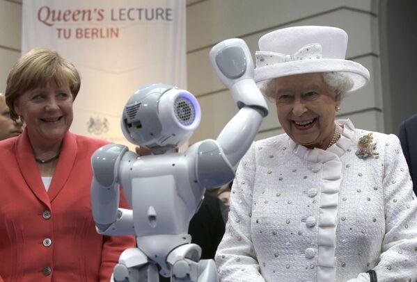 Канцлер Германии Ангела Меркель и королева Великобритании Елизавета II улыбаются, когда маленький робот машет британской королеве во время приема в Техническом университете в Берлине. 2015 год. - Sputnik Таджикистан