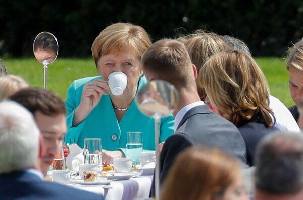 """Канцлер Германии Ангела Меркель пьет кофе на мероприятии """"журнальный столик"""", организованном главой Германии в честь 70-летия Конституции в саду президентского дворца. 23 мая 2019 года. - Sputnik Таджикистан"""