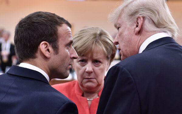 Президент США Дональд Трамп, президент Франции Эммануэль Макрон и канцлер Германии Ангела Меркель во время напряженного разговора в начале первой рабочей сессии встречи G20 в Гамбурге, 7 июля 2017 года. - Sputnik Таджикистан