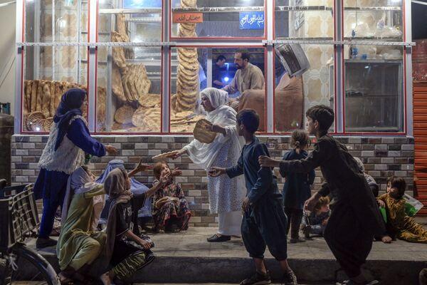 Женщина раздает лепешки детям. - Sputnik Таджикистан