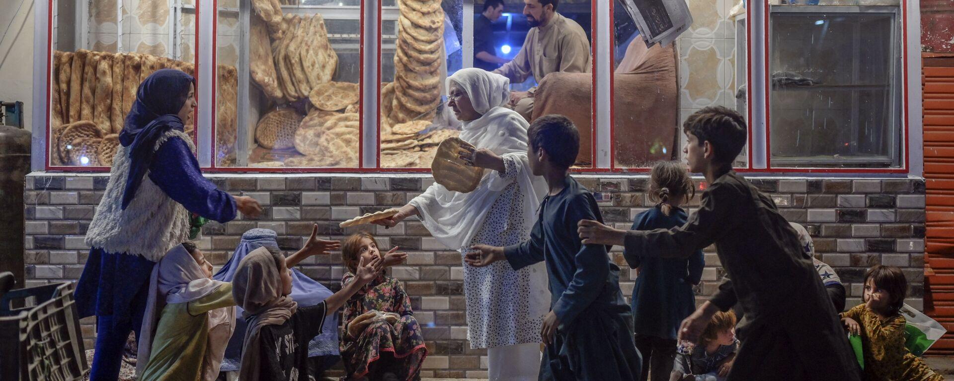 Женщина раздает хлеб нуждающимся детям перед пекарней в Кабуле - Sputnik Тоҷикистон, 1920, 07.10.2021
