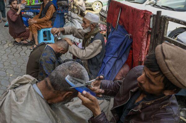 Уличные парикмахеры обслуживают жителей. Как сообщают СМИ, профессиональные барберы потеряли большинство своих клиентов. - Sputnik Таджикистан