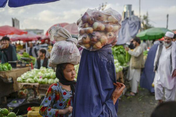 Женщина в парандже несет на голове мешок с луком, идя по рынку. - Sputnik Таджикистан