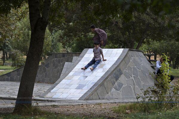 Дети играют на горке в столичном парке. - Sputnik Таджикистан