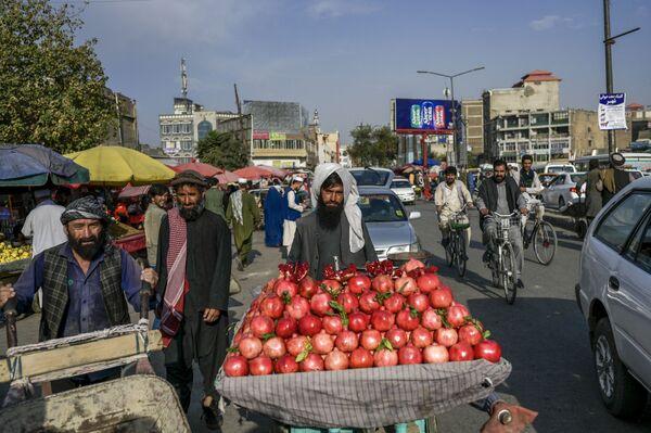 Продавец гранатов с передвижной витриной ищет покупателей на рынке. - Sputnik Таджикистан