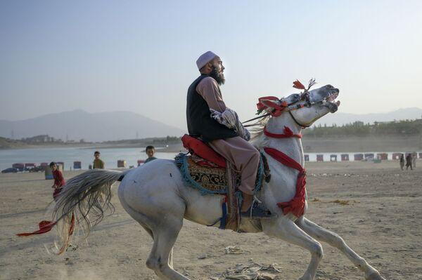 "Член ""Талибана""* катается на лошади у водохранилища Каргха на окраинах Кабула. - Sputnik Таджикистан"