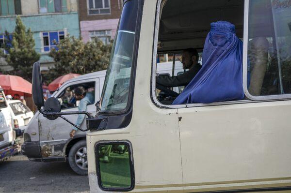 Женщина в полной парандже едет в общественном транспорте. - Sputnik Таджикистан