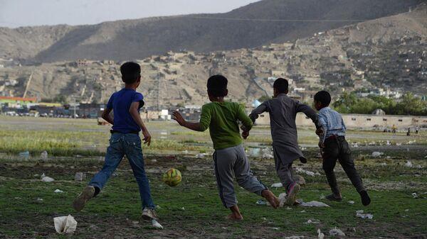 Афганские дети играют в футбол на поле в Кабуле, архивное фото - Sputnik Таджикистан