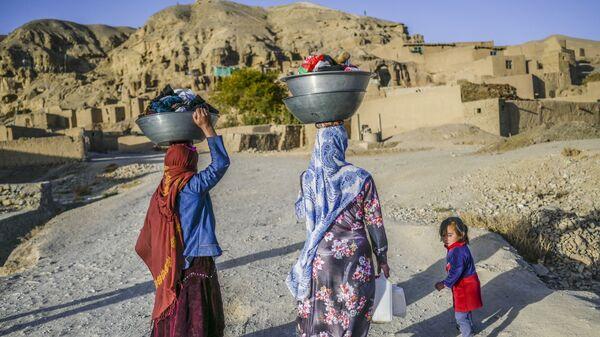 Хазарейцы с бельем у пещерных домов в афганском Бамиане  - Sputnik Тоҷикистон