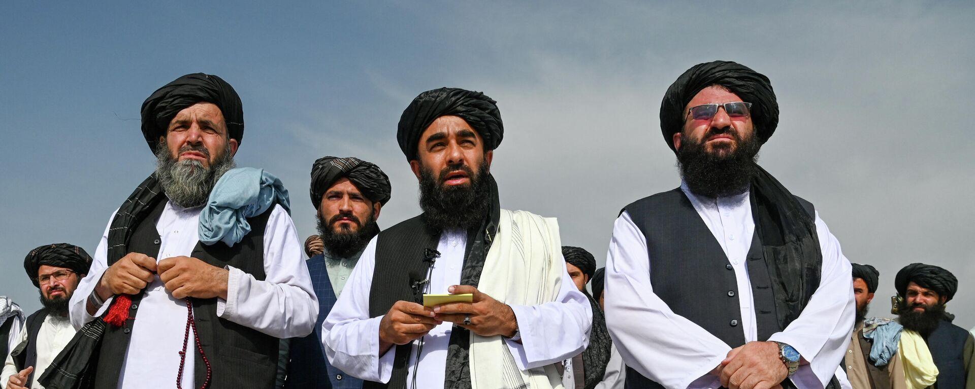 Представитель Талибана Забихулла Муджахид (в центре) обращается к СМИ в аэропорту Кабула - Sputnik Тоҷикистон, 1920, 12.10.2021