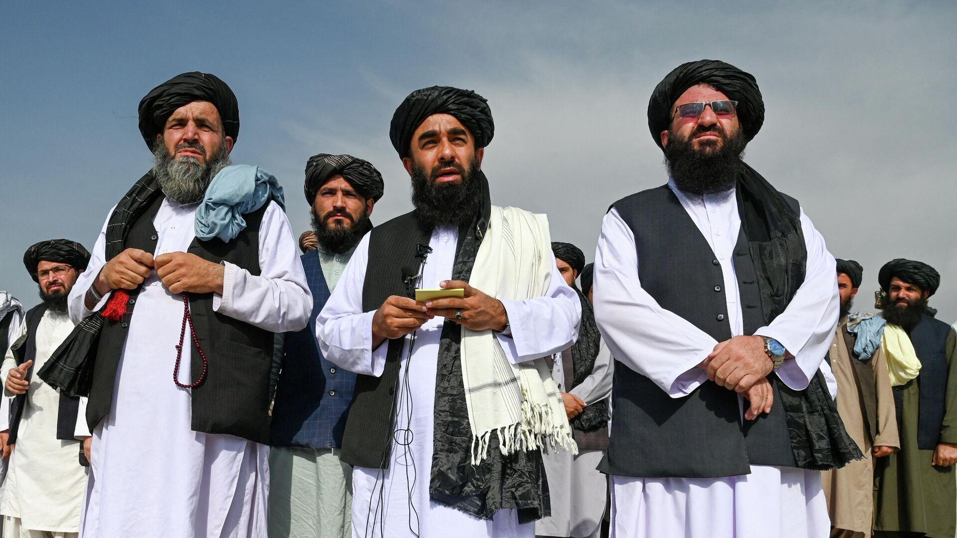 Представитель Талибана Забихулла Муджахид (в центре) обращается к СМИ в аэропорту Кабула - Sputnik Тоҷикистон, 1920, 10.10.2021