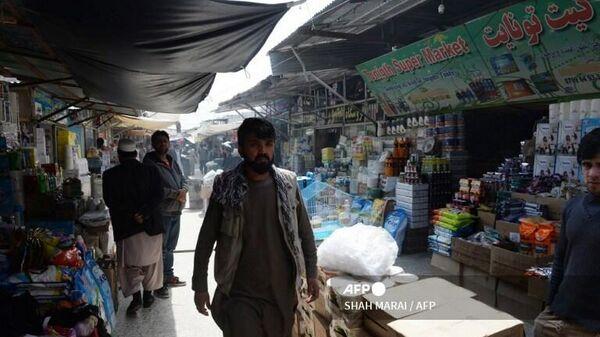Житель Афганистана проходит через рынок Буша в Кабуле - Sputnik Таджикистан