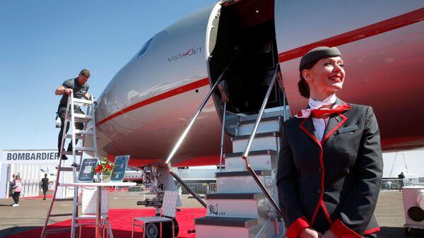 Стюардесса у бизнес-джета VistaJet Global 7500 на выставке в Хендерсоне, штат Невада  - Sputnik Тоҷикистон