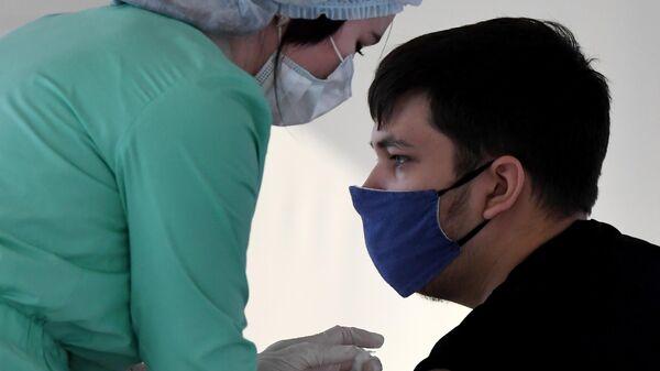 Молодой человек вакцинируется от Covid-19 в круглосуточном пункте вакцинации - Sputnik Таджикистан