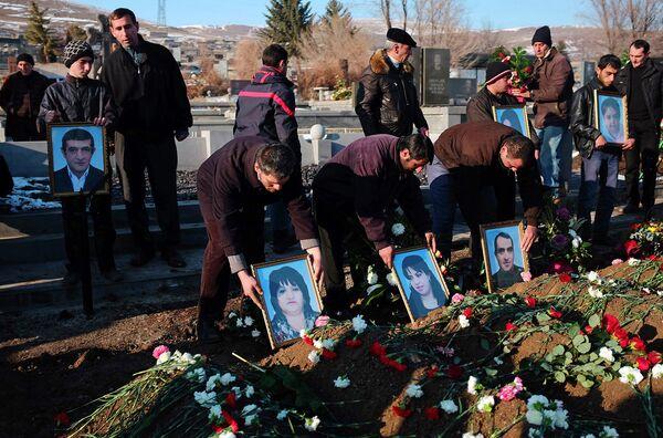 Люди держат портреты шестерых погибших членов семьи Аветисян во время церемонии похорон в Гюмри. 15 января 2015 года. - Sputnik Таджикистан