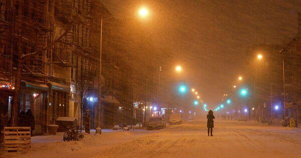 Человек стоит среди заснеженной улицы Нью-Йорка во время сильного снегопада 27 января 2015 года - Sputnik Таджикистан
