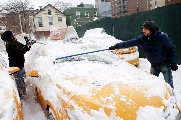 Мужчина чистит автомобиль после сильного снегопада. 27 января 2015 г. - Sputnik Таджикистан