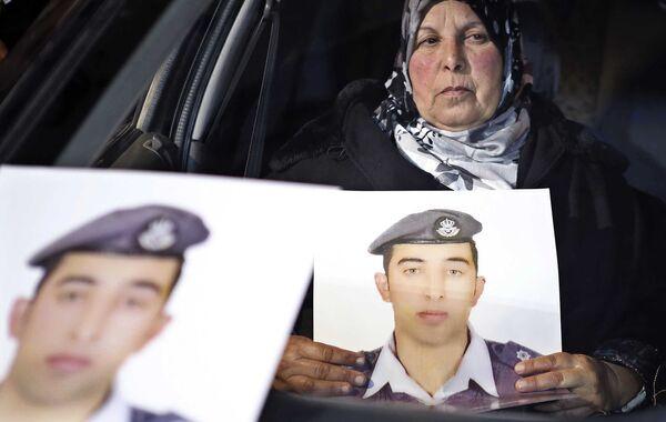 Женщина держит в руках фотографию своего сына, иорданского летчика, захваченного террористами ИГ - Sputnik Таджикистан