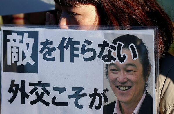 Женщина держит в руках плакат с портретом журналиста Кэндзи Гото, казненного боевиками Исламского государства. Архивное фото - Sputnik Таджикистан